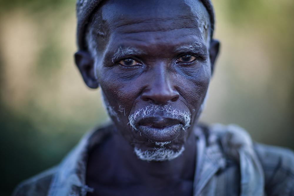 Ablaye Moussa, a farmer at the end of a day picking cotton. Cotton is grown in open fields and there is no shade from the sun so the work is hot. The labour of cotton picking in this region is done traditionally as a favour that is paid with food and drink and reciprocity. Land is owned individually in small plots.