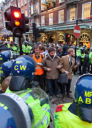 © licensed to London News Pictures. London, UK 08/05/11. Protesters link arms as they end their occupation of Fortnum and Mason during protests on 26th March. Police photographed and arrested each protester as they left the store. A protest is due to be held outside a City of Westminster Court hearing tomorrow (9th May) in support of UKUncut protesters who occupied Fortnum and Mason during protests in London on 26th March. Protesters say the 26th March demonstration in Fortnum & Mason was peaceful, that they were protesting lawfully, that police told them they'd be free to leave before arresting them and that they should not be prosecuted. FILE PICTURE DATED 26/03/2011. Please see special instructions for usage rates. Photo credit should read Joel Goodman/LNP