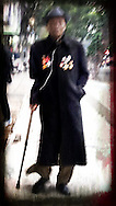 Blurred portrait of a Vietnamese man wearing a jacket decorated with metals and walking with a cane around downtown Hanoi, Vietnam, Southeast Asia