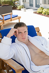 handsome man in a white robe relaxing in a lounge chair at a hotel