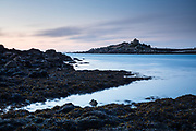 Dusk hues over Northwethel island. Captured from Old Grimsby Harbour on Tresco. Dense seaweed cover provides fantastic texture to the foreground. Isles of Scilly, Cornwall, UK