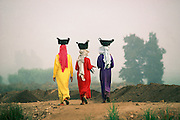 Egypt, 2000 - Three local girls in colorful dresses walk through the Mendes dig site while balancing baskets on their heads. The baskets are filled with earth from excavation at the dig site near Mansura in the Nile Delta. The bright yellow, red, and purple dresses are the girls work clothes.
