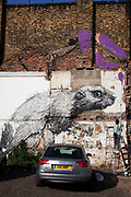 Roa is a Belgian street artist renowned for his giant black and white animals which can be found on walls and shutters in varying states of decay. Here seen is a beaver character in a parking lot on Hackney Road as another artist paints around it. There are also a few Rats and Birds which reside on shop shutters along Brick Lane.<br /> <br /> Street art in the East End of London is an ever changing visual enigma, as the artworks constantly change, as councils clean some walls or new works go up in place of others. While some consider this vandalism or graffiti, these artworks are very popular among local people and visitors alike, as a sense of poignancy remains in the work, many of which have subtle messages.
