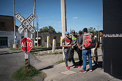 A group of migrant workers  wait for a train heading north in Apizaco, Mexico. They have been trvelling for a month already and are about half way. Everyone in the group has worked in at least one trade, and they are hoping to find work in the US.