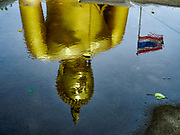 17 JULY 2017 - HUA TAPHON, ANG THONG, THAILAND: The big Buddha statue reflected in a rain puddle at Wat Muang in Ang Thong Province. The statue stands 92 m (300 ft) high, and is 63 m (210 ft) wide. Construction started in 1990, and completed in 2008. It is made of concrete and painted gold. It is the largest statue in Thailand and one of the largest statues in the world. The temple is renowned for the statue and its statue garden, which represents the Thai version of a hellish afterlife.     PHOTO BY JACK KURTZ