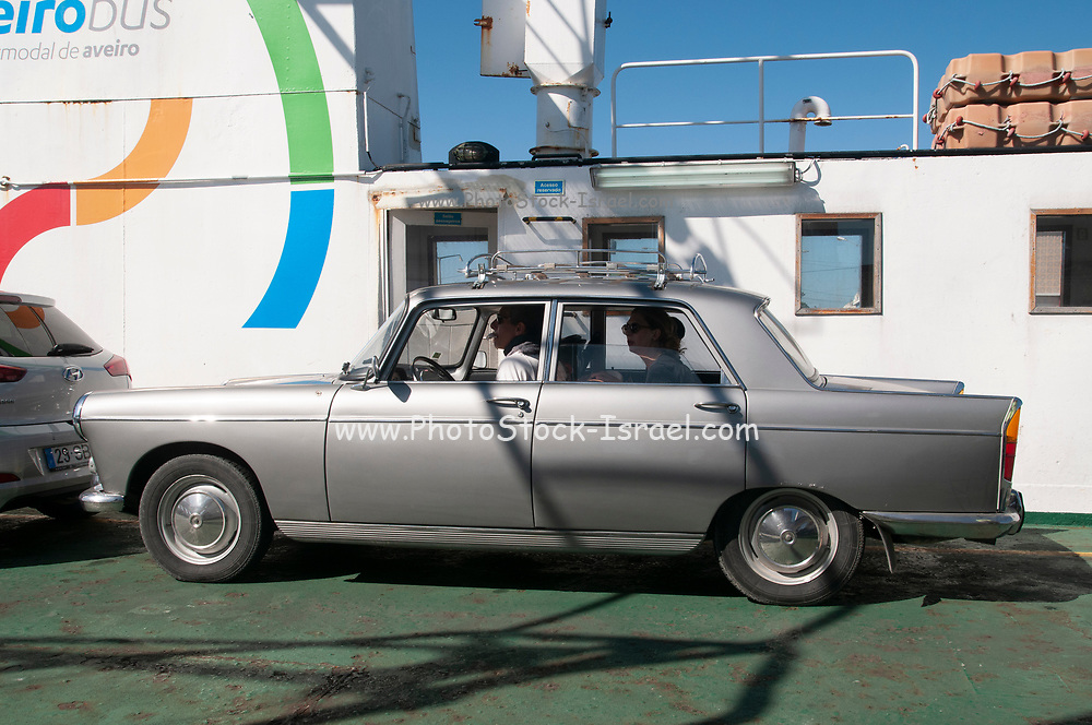 classic car Peugeot 404 onboard the cars and passengers ferry between Sao Jacinto and Barra in Ria de Aveiro, Portugal.