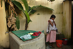 Shrianna Barthelot, 11, waits for her turn to bathe at a relative's house, Batticaloa, Sri Lanka, Jan. 28, 2005. She and her sister Brianna, 13, not pictured here, lost both parents and their older brother in the tsunami. They are now living with relatives at night and spending most of their days at the convent where the rest of their village is staying. Residents of the small Christian village Dutch Bar spent more than six weeks in a makeshift refugee camp at the local convent recovering from the devastating tsunami that hit the eastern and southern borders of Sri Lanka. They were then moved into another temporary living camp, while awaiting the building of new homes. More than 150 members in this community of less than 1000 people died in the tragic event.