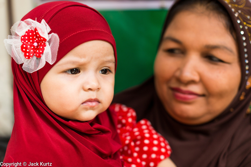 "08 AUGUST 2013 - BANGKOK, THAILAND: A woman and her daughter at Eid al-Fitr observances at Haroon Mosque in Bangkok. Eid al-Fitr is the ""festival of breaking of the fast,"" it's also called the Lesser Eid. It's an important religious holiday celebrated by Muslims worldwide that marks the end of Ramadan, the Islamic holy month of fasting. The religious Eid is a single day and Muslims are not permitted to fast that day. The holiday celebrates the conclusion of the 29 or 30 days of dawn-to-sunset fasting during the entire month of Ramadan. This is a day when Muslims around the world show a common goal of unity. The date for the start of any lunar Hijri month varies based on the observation of new moon by local religious authorities, so the exact day of celebration varies by locality.      PHOTO BY JACK KURTZ"