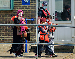 © Licensed to London News Pictures. 20/07/2021. Dover, UK. A migrant family is escorted by Border Force officers as they are brought ashore at Dover Harbour in Kent after crossing the English Channel. It is being reported that at least 430 migrants crossed the English Channel to the UK on Monday, a new single day record. Photo credit: Stuart Brock/LNP
