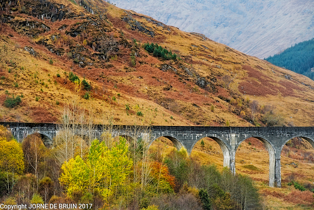 The famous Glenfinnan railway bridge in Scotland, also featured in the Harry Potter movies, in autumn.