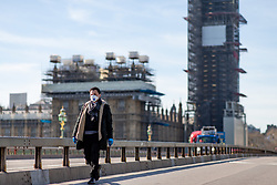© Licensed to London News Pictures. 23/03/2020. LONDON, UK. A man walks along a quiet Westminster Bridge this afternoon. The government has advised people to practice social distancing measures that help reduce the transmission of Coronavirus (COVID-19). Photo credit: Luke Dray/LNP