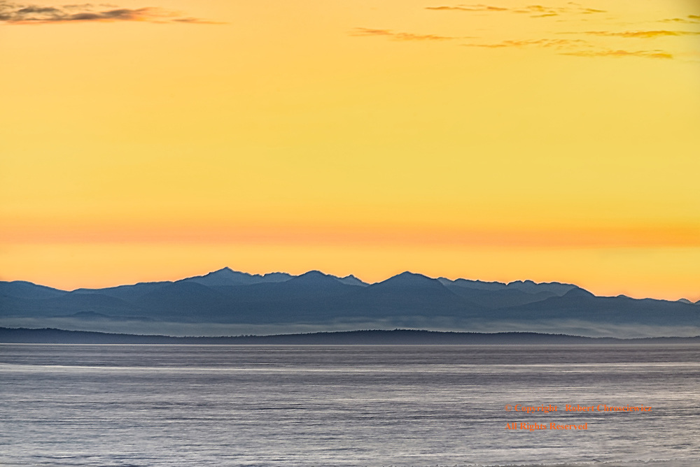 Island Sunset: The silhouette of Vancouver Island at sunset, from Vancouver British Columbia Canada.
