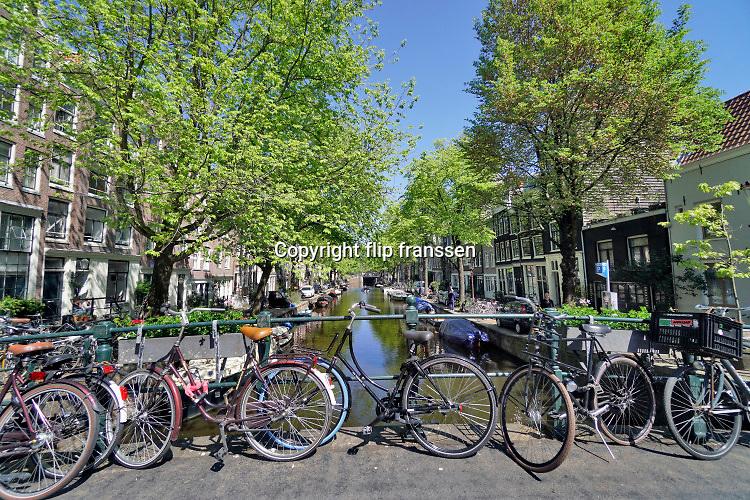 Nederland, Amsterdam, 7-5-2020 De regering laat het normale dagelijks leven weer langzaam opstarten . Door de afwezigheid van toeristen is het ongewoon rustig op de wallen en de rest van de binnenstad van Amsterdam en is de stad te zien zoals die pakweg voor de eeuwwisseling was . Op de bruggetjes over de grachten staan fietsen . Bruggetje,fiets,gracht,grachten,grachtenbrug, typisch,amsterdams,iconisch,historische,bebouwing,architectuur .  Unlock,beperkende,beperkingen, opheffen,versoepelen,versoepeling , opengooien, massatoerisme,toeristisch, toeristische,  Foto: Flip Franssen