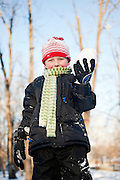 A 4-year-old boy plays holds a snowball while playing in the snow.