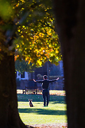 A man's terrier waits patiently in the sunshine as he does stretches in Queens Park, North West London as the early morning sunshine illuminates the leaves of trees as autumn colours begin to set in. London, October 01 2018.