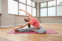 Pregnant woman practicing Yoga exercise stretching