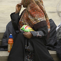 Young muslim girls wearing hijab, eating crisps at Eid in the Square, London, England<br />
