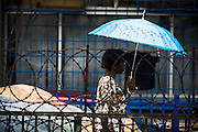A woman holding an umbrella walks by a barb wire fence in central Accra, Ghana on Tuesday June 16, 2009.