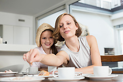 Mother and daughter at table eating cake
