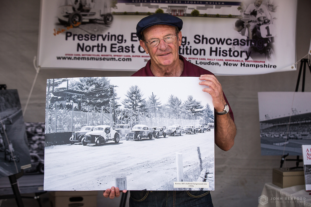 Motorsports announcer and magazine editor Dick Berggren holds a photo of a historic race at the New England Motor Sports Museum booth at New Hampshire Motor Speedway during the NH 301 NASCAR race.