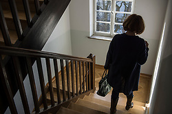 Rear view of senior woman wearing winter coat moving down on a staircase, Munich, Bavaria, Germany