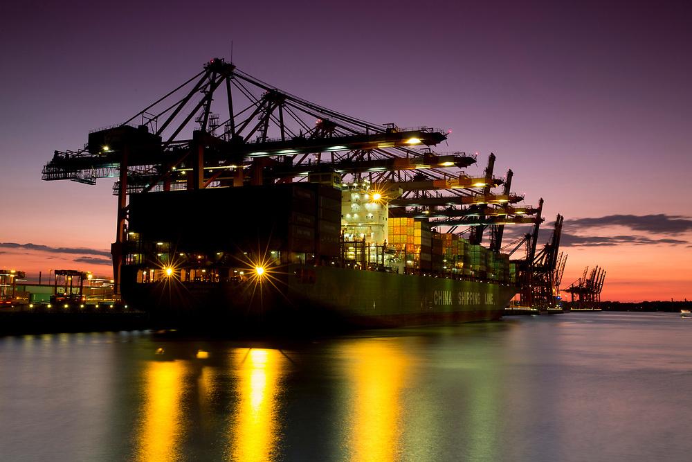 Blick auf die Containerschiffe bei der HHLA im Hafen Waltershof während Sonnenuntergang