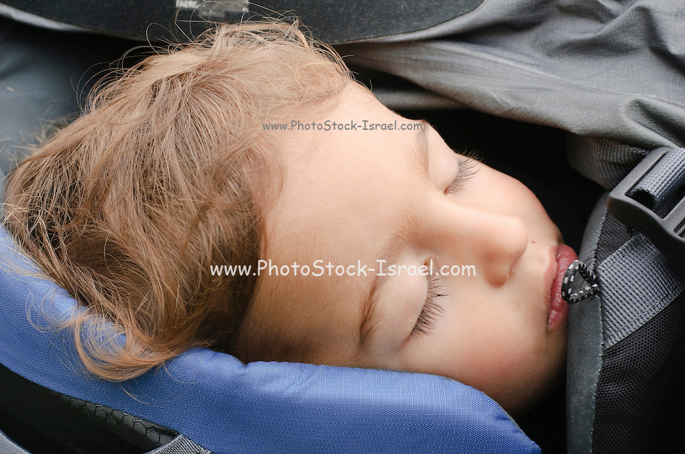 Boy of two asleep in a backpack baby carrier. Photogrpahed in the Austrian Alps