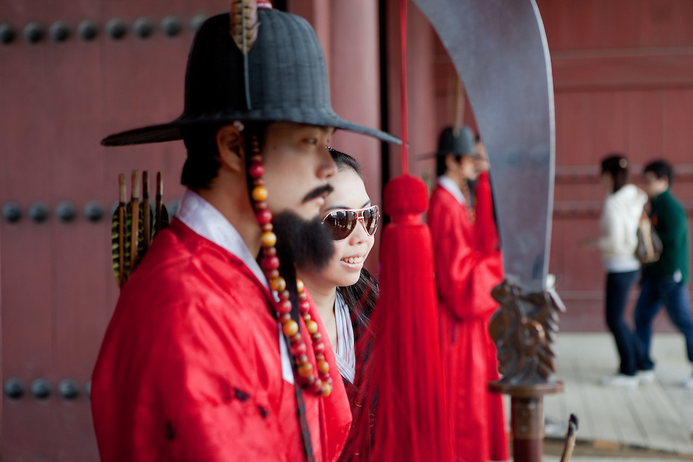 Woman inbetween guards at the ceremony of opening and closing the main palace gate and gate guard change at Gwanghwamun of Gyeongbokgung Palace, the main royal palace of Joseon Dynasty, the spectacle is based on the formality from the early 15th century. / Seoul, South Korea, Republic of Korea, KOR, 25 April 2010.