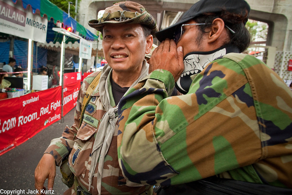 """May 12 - BANGKOK, THAILAND: Maj. Gen. KHATTIYA """"Seh Daeng"""" SAWASDIPOL (LEFT) talks to a Red Shirt security official at a Red Shirt barricade in the Red Shirt camp in Bangkok Wednesday. Seh Daeng, as he is known, has emerged as the Red Shirts unofficial military commander. He has organized the barricades that ring the Red Shirt camp and has threatened to organize a guerilla campaign against the government if the Red Shirt protest is crushed by force. Seh Daeng is a hero to many Thais because he is credited with crushing Thailand's communist insurgency in the 1970's and 80's. He was the commander of Thailand's Internal Security Operations Command but after his political activities became apparent he was made the head aerobics instructor for the Thai army. He is now seen as one of the major personalities destabilizing the country and the government alleges that he is behind many of the grenade attacks and drive by shootings directed at government buildings and officials and he is wanted for a long list of felony offenses including weapons charges and terrorism related charges. Although some Red Shirts have officially repudiated him, he is still frequently seen around the Reds' barricades. The army has started proceedings to fire him, but he remains a general on active duty.   Photo by Jack Kurtz"""