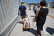 A young girl rests on her father's rolling suitcase as they exit the airport in Tianjin, China on 16 July 2013.