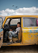 Young unemployed sitting in a yellow car. In and around Bulunkul village.<br /> <br /> Driving on the Pamir Highway (M41) from Khorog through the Pamir mountains.<br /> <br /> Tajikistan, a mountainous landlocked country in Central Asia. Afghanistan borders it to the south, Uzbekistan to the west, Kyrgyzstan to the north, and People's Republic of China to the east. Tajikistan also lies adjacent to Pakistan separated by the narrow Wakhan Corridor.<br /> Tajikistan became a republic of the Soviet Union in the 20th century, known as the Tajik Soviet Socialist Republic.<br /> It was the first of the Central Asian republic to gain independence in December 1991.