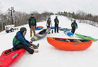 Christopher Freeman takes off his boats in preparation of his kayak run down the snow course during the 3rd annual Boat Bash Snow Crash event with Franklin's Mill City Park at the Veteran's Memorial Ski Hill on Saturday afternoon.  (Karen Bobotas/for the Laconia Daily Sun)