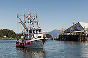 A fishing boat enters the docks in the tiny village of Petersburg on Mitkof Island along the Wrangell Narrows in Frederick Sound with the Alaska Coast Range of mountains behind on Mitkof Island, Alaska. Petersburg settled by Norwegian immigrant Peter Buschmann is known as Little Norway due to the high percentage of people of Scandinavian origin.