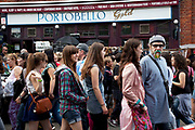 Scene on Portobello Road market, Notting Hill, West London. This famous Saturday market is when the antique stalls line the streets as well as the food stalls further down the hill. This is classic London with busy crowds of people coming to hang out, maybe buy something, or just browse the stalls and have some food.