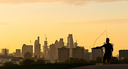 London, September 11 2017. A man on Primrose Hill exercises with a skipping rope against the backdrop of the London skyline as a new day breaks over the city. © Paul Davey
