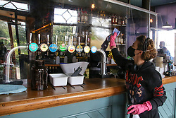 © Licensed to London News Pictures. 08/04/2021. London, UK. A member of staff cleans the plastic window at The Finsbury Pub in Finsbury Park, north London, as pubs with beer gardens prepare to re-open on Monday 12 April, following the easing of Covid-19 lockdown restrictions. Photo credit: Dinendra Haria/LNP