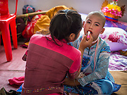 "05 APRIL 2015 - CHIANG MAI, CHIANG MAI, THAILAND: Tai Yai women get the boys in their family ready to be ordained as Buddhist novices during the second day of the three day long Poi Song Long Festival in Chiang Mai. The Poi Sang Long Festival (also called Poy Sang Long) is an ordination ceremony for Tai (also and commonly called Shan, though they prefer Tai) boys in the Shan State of Myanmar (Burma) and in Shan communities in western Thailand. Most Tai boys go into the monastery as novice monks at some point between the ages of seven and fourteen. This year seven boys were ordained at the Poi Sang Long ceremony at Wat Pa Pao in Chiang Mai. Poy Song Long is Tai (Shan) for ""Festival of the Jewel (or Crystal) Sons.    PHOTO BY JACK KURTZ"