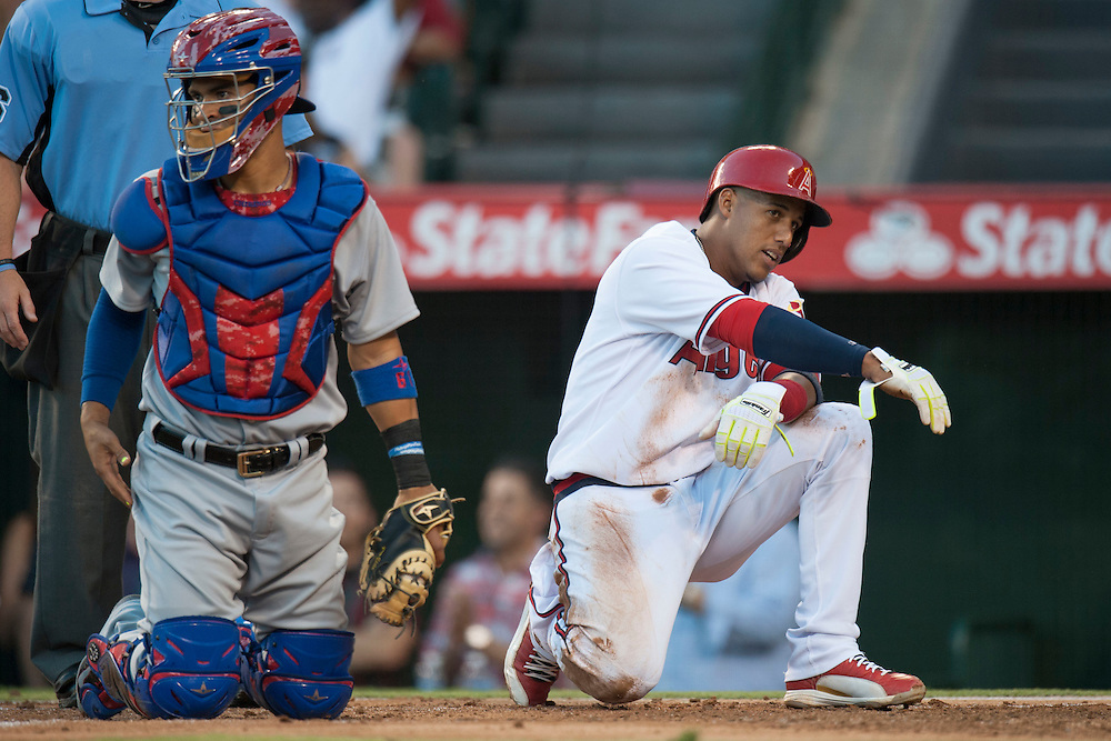 The Angels' Yunel Escobar relaxes at home after scoring past Texas catcher Robinson Chirinos in the first inning at Angel Stadium on Wednesday.<br /> <br /> ///ADDITIONAL INFO:   <br /> <br /> angels.0721.kjs  ---  Photo by KEVIN SULLIVAN / Orange County Register  -- 7/20/16<br /> <br /> The Los Angeles Angels take on the Texas Rangers at Angel Stadium.