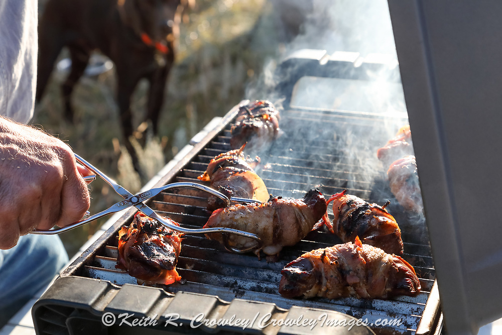 Grouse breasts grilling during a Montana prairie grouse hunt.
