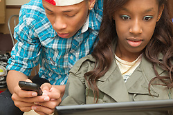 Teenage girl on laptop computer, with teenage boy on mobile phone. (This photo has extra clearance covering Homelessness, Mental Health Issues, Bullying, Education and Exclusion, as well as the usual clearance for Fostering & Adoption and general Social Services contexts,)