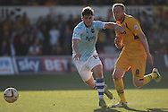 Jordan Moore-Taylor of Exeter (l) attempts to shield the ball from Lee Minshull of Newport. Skybet football league two match, Newport county v Exeter city at Rodney Parade in Newport, South Wales on Sunday 16th March 2014.<br /> pic by Mark Hawkins, Andrew Orchard sports photography.
