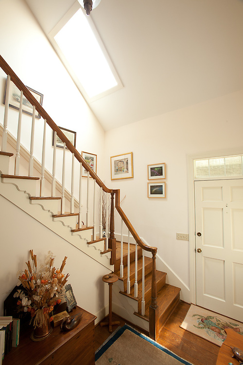 The bright, front on entrance hall features stairs, a balcony and a skylight in the main house at 33 Pine View Drive.