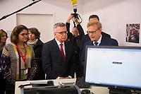 DEU, Deutschland, Germany, Berlin, 06.12.2017: Bundesinnenminister Dr. Thomas de Maiziere (CDU) zu Besuch im Bundesamt für Migration und Flüchtlinge (BAMF). Projektsteuerer Justus Strübing (r.), IT-Chef Markus Richter (2.v.r.), und Sachbearbeiterin Sawsen Barakat (l.) informieren den Minister zu neuen IT-Assistenzsystemen, die seit September 2017 im BAMF zum Einsatz kommen. Diese Assistenzsysteme (u.a. Bildbiometrie, und das Auslesen von mobilen Datenträgern) leisten Hilfestellung bei der Identitätsfeststellung und -plausibilisierung von Asylantragstellern.