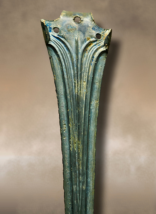 Hittite bronze decorated sword blade close up with writing. Hittite Period 1650 - 1450 BC.  Hattusa Boğazkale. Çorum Archaeological Museum, Corum, Turkey. Against a warm art bacground. .<br />  <br /> If you prefer to buy from our ALAMY STOCK LIBRARY page at https://www.alamy.com/portfolio/paul-williams-funkystock/hittite-art-antiquities.html  - Type Hattusa into the LOWER SEARCH WITHIN GALLERY box. Refine search by adding background colour, place,etc<br /> <br /> Visit our HITTITE PHOTO COLLECTIONS for more photos to download or buy as wall art prints https://funkystock.photoshelter.com/gallery-collection/The-Hittites-Art-Artefacts-Antiquities-Historic-Sites-Pictures-Images-of/C0000NUBSMhSc3Oo