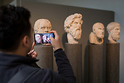 A visitor takes a picture of the heads of ancient Greek Hellenistic philosophers L-R: Sokrates, Antisthenes, Chrysippus and Epikouros, in the British Museum, on 11th April 2018, in London, England.