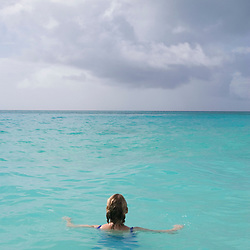 A woman swims in the clear blue waters of the Caribbean on the island of Antigua.