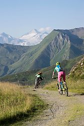 Rear view of mountain bikers riding on hill, Zillertal, Tyrol, Austria