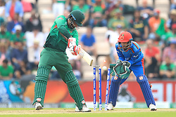 Bangladesh's Tamim Iqbal (left) is bowled out by Afghanistan Mohammad Nabi during the ICC Cricket World Cup group stage match at The Hampshire Bowl, Southampton.
