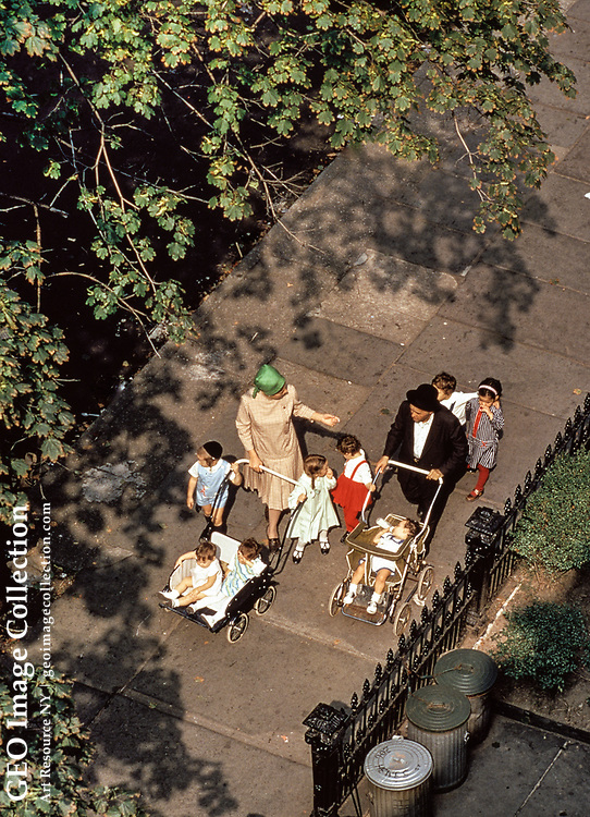 An observant Jewish family with eight children stroll down the sidewalk with strollers in Williamsburg, Brooklyn, New York on October 20, 1972. Religious Ashkenazi Jews in the Diaspora often have many children to compensate for co-religionists lost in the Holocaust. The wide sidewalks in 19th century residential neighborhoods are friendly to large families on leisure walks.