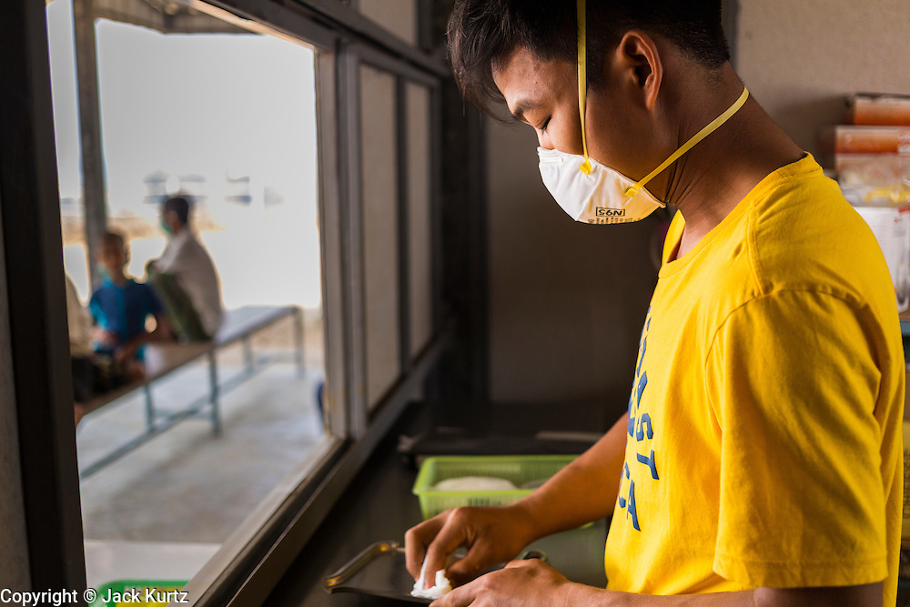 03 MARCH 2104 - MAE KASA, TAK, THAILAND:  A worker in the pharmacy counts out patients' medications at the Sanatorium Center for Border Communities in Mae Kasa, about 30 minutes north of Mae Sot, Thailand. The Sanatorium provides treatment and housing for people with tuberculosis in an isolated setting for about 68 patients, all Burmese. The clinic is operated by the Shoklo Malaria Research Unit and works with several other NGOs that assist Burmese people in Thailand. Reforms in Myanmar have alllowed NGOs to operate in Myanmar, as a result many NGOs are shifting resources to operations in Myanmar, leaving Burmese migrants and refugees in Thailand vulnerable. Funding cuts could jeopardize programs at the clinic. TB is a serious health challenge in Burma, which has one of the highest rates of TB in the world. The TB rate in Thailand is ¼ to ⅕ the rate in Burma.        PHOTO BY JACK KURTZ